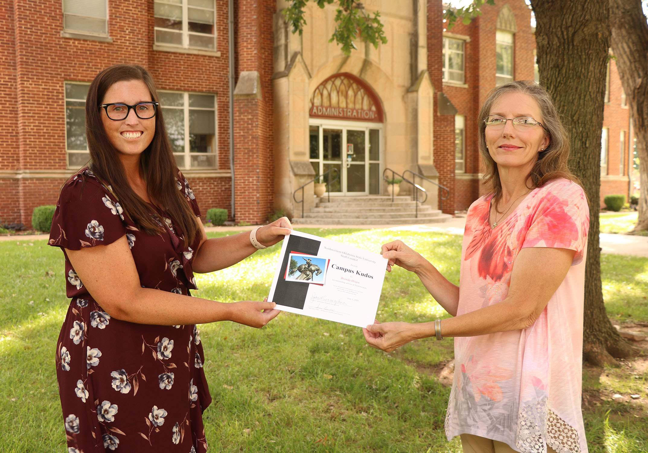 Sue Burks (right) presents Brenda Hearn with a spring Campus Kudos Award.